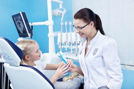 Office uniforms: Dentista da al paciente un cepillo de dientes y pasta de dientes