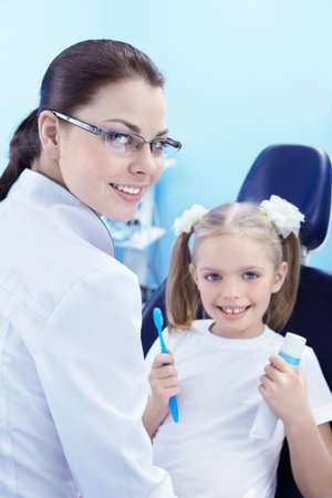A child in a dental chair with a toothbrush and toothpaste photo