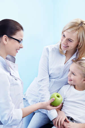 The doctor gives the child a green Apple photo