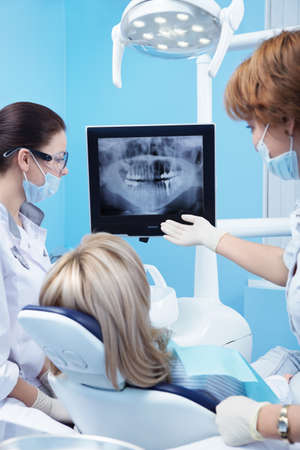dentists surgery: Dentist shows a patient x-ray of teeth Stock Photo