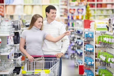 supermercado: Chica atractiva muestra a un hombre en la direcci�n de la tienda
