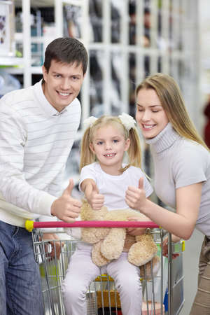 A happy family shows thumbs up at the store photo