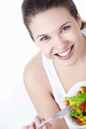 dieta sana: Atractiva joven comiendo ensalada sobre un fondo blanco