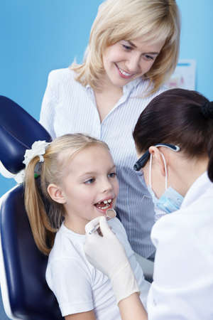 The dentist makes examination of the child photo