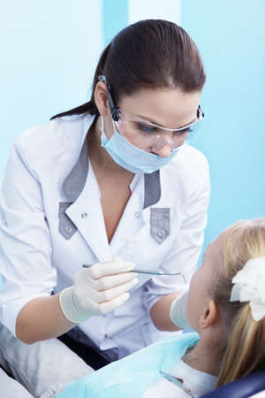 The dentist examines a child in dentistry photo