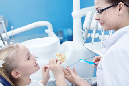 The dentist and child in the dental office photo