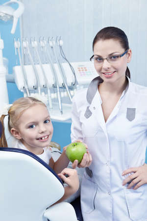 Dentist gives the child a green Apple photo
