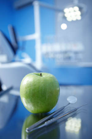 Apple and dental instruments in the foreground Stock Photo