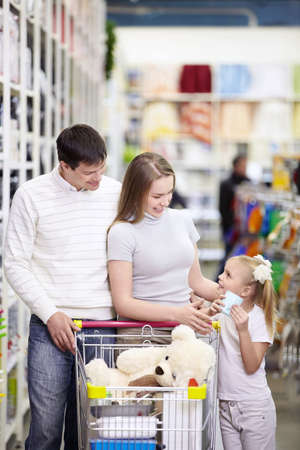 woman shopping cart: A young family is shopping in a store