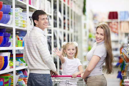 supermarket cart: A happy family is shopping in a store