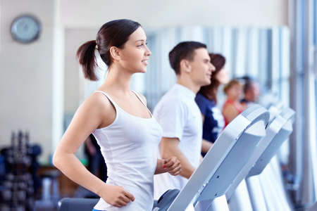 Attractive people on the treadmill photo