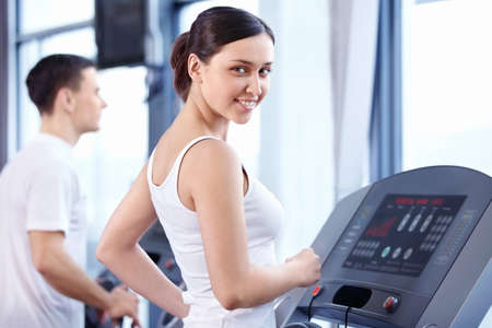 An attractive young woman on a treadmill Stock Photo