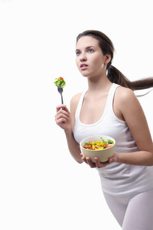 Attractive girl running with a plate of salad on a white background photo
