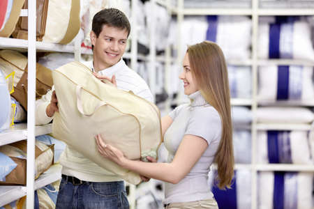 white pillow: Man gives a girl the pillow in the store