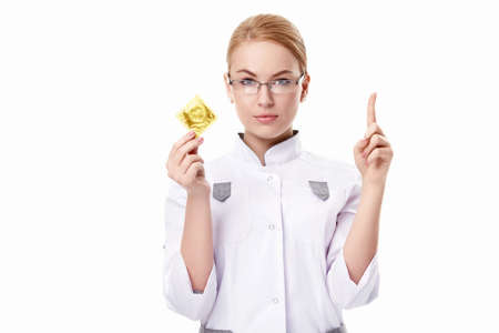 A young doctor with a condom on a white background photo