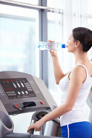 Young attractive girl drinks water in the fitness club photo