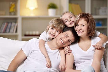familia abrazo: Riendo a familias con ni�os en su casa en la noche Foto de archivo