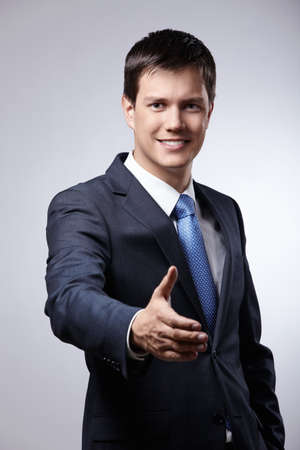 Young businessman in a suit holds out his hand for a handshake Stock Photo - 8962033