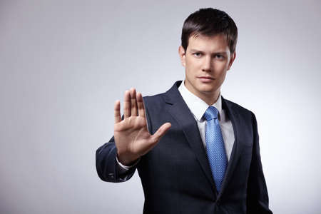 stop hand: Young businessman in a suit shows his hand