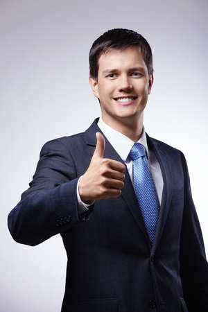 thumb up: Attractive man in a suit with a thumb up on a gray background Stock Photo