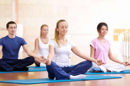 meditating woman: Attractive young people meditate