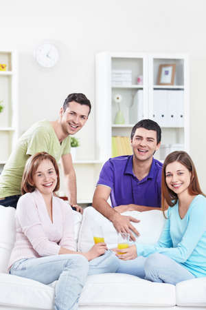 Young attractive people drink juice in the apartment Stock Photo - 8969161
