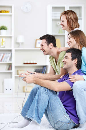 playstation: Young friends playing video games at home