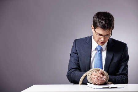 Mature businessman signs a document with tied hands photo