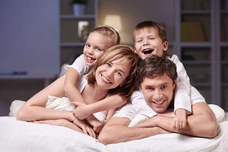 Families with children in bed at night at home Stock Photo