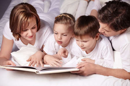 Parents of children reading a book in bed photo