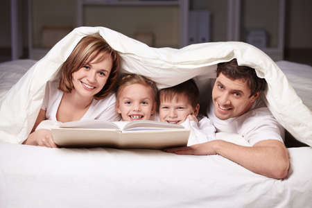 Parents and children with a book under a blanket photo