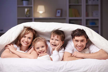 indoor: Families with children in bed under a blanket