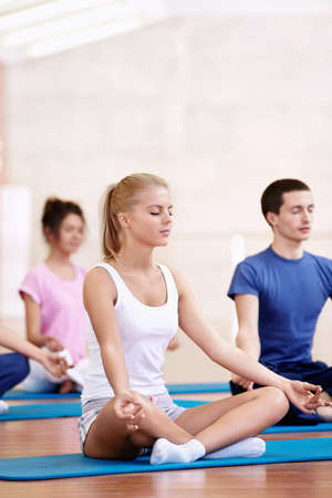 Young attractive people do yoga photo