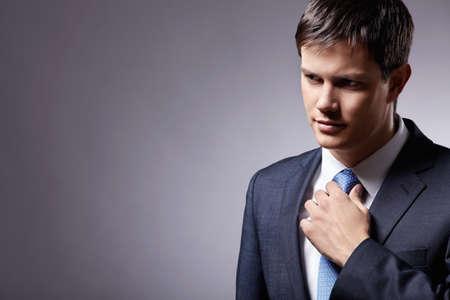 gray suit: Attractive man in a suit straightens his tie