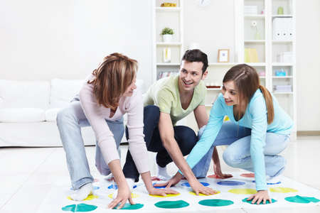 twister: Young happy people playing twister at home