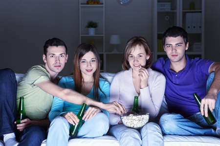 Young attractive people watch movies at home photo