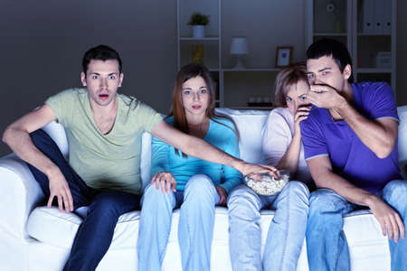Young attractive people are watching TV at home photo
