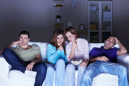 Young attractive friends watch movies at home photo