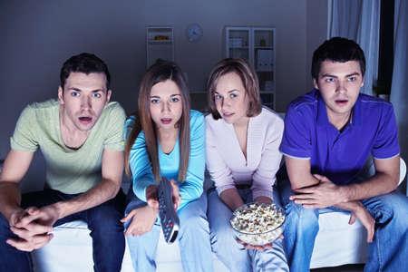 pareja viendo tv: J�venes amigos atractivo reloj en asombro en la TV Foto de archivo