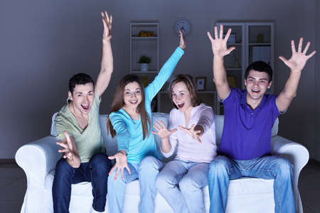 Young happy friends are watching TV at home Stock Photo - 8969337