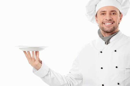 chef uniform: Attractive cook holding an empty plate on a white background