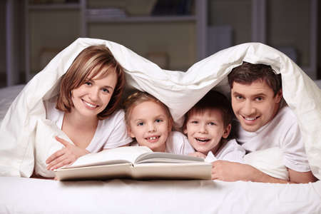 white blanket: Parents with children under the blanket with a book