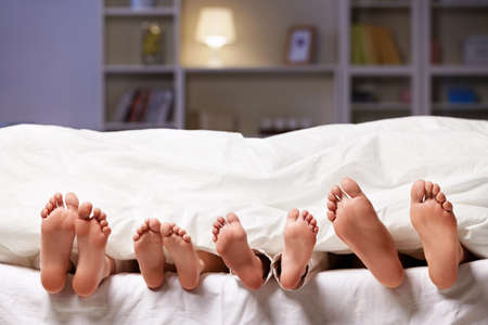 young girl feet: Feet sticking out from under the blanket