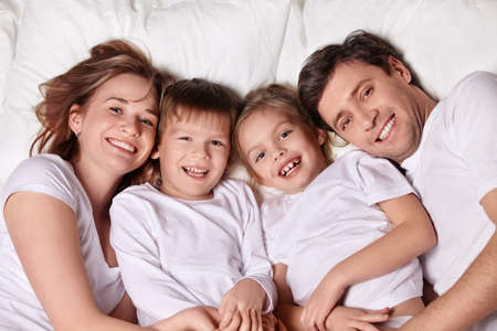 Smiling family in bed Stock Photo - 9075221