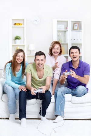 Young beautiful friends play video games at home photo