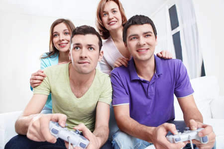 Young  friends play video games at home photo