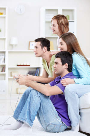 playstation: Happy friends play video games at home