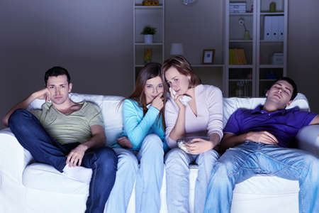 Young people watch a sad movie at home photo