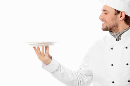 chef uniform: A smiling cook looks at the empty plate on a white background Stock Photo