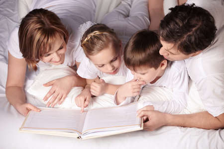 Parents of children reading a book photo